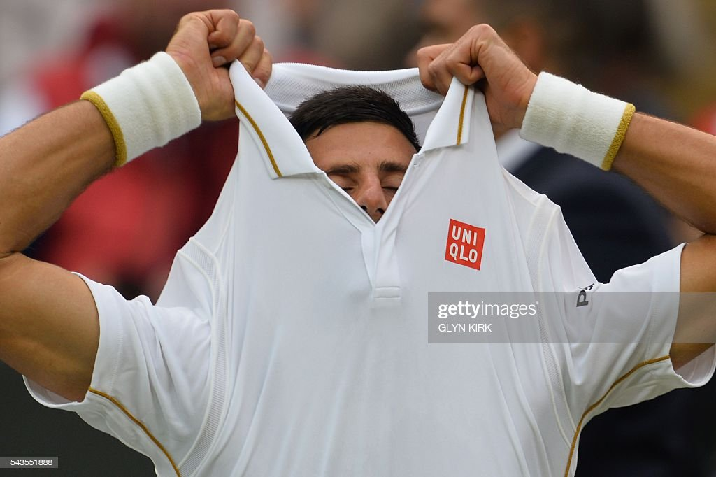 Serbia's Novak Djokovic changes his shirt in the break between games against France's Adrian Mannarino during their men's singles second round match on the third day of the 2016 Wimbledon Championships at The All England Lawn Tennis Club in Wimbledon, southwest London, on June 29, 2016. / AFP / GLYN