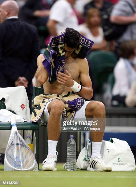 Serbia's Novak Djokovic changing his shirt and towels off during his match against USA's Bobby Reynolds during day four of the Wimbledon...