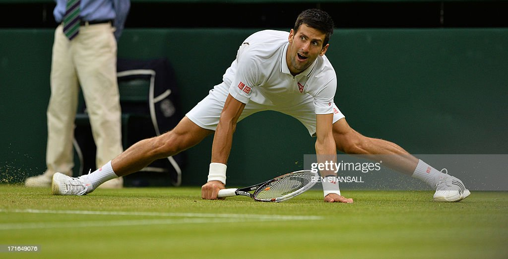 Serbia's Novak Djokovic does the splits as he stretches for a return against US player Bobby Reynolds during their second round men's singles match on day four of the 2013 Wimbledon Championships tennis tournament at the All England Club in Wimbledon, southwest London, on June 27, 2013. AFP PHOTO / BEN STANSALL - RESTRICTED TO EDITORIAL USE