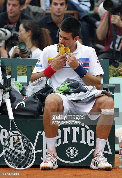 Serbia's Novak Djokovic eats a banana as he plays with Switzerland's Roger Federer during a semi final at the French Open tennis championship at the...