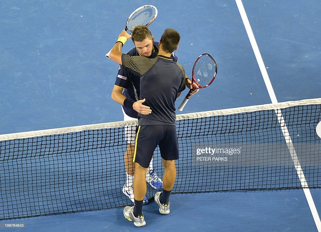 Serbia's Novak Djokovic (R) embraces Switzerland's Stanislas Wawrinka after his victory during their men's singles match on day seven of the Australian Open tennis tournament in Melbourne early on January 21, 2013.