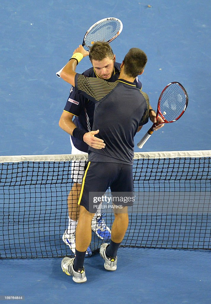 Serbia's Novak Djokovic (R) embraces Switzerland's Stanislas Wawrinka after his victory during their men's singles match on day seven of the Australian Open tennis tournament in Melbourne early on January 21, 2013. AFP PHOTO / PETER PARKS IMAGE STRICTLY RESTRICTED TO EDITORIAL USE - STRICTLY NO COMMERCIAL USE