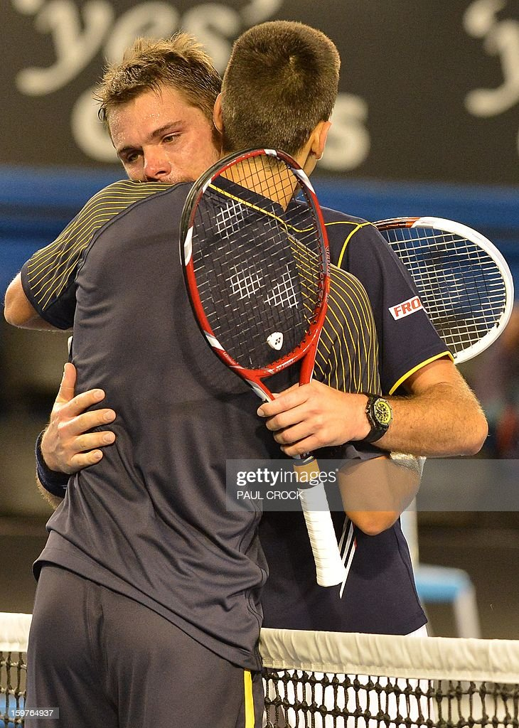 Serbia's Novak Djokovic (R) embraces Switzerland's Stanislas Wawrinka (L) after his victory during their men's singles match on day seven of the Australian Open tennis tournament in Melbourne early on January 21, 2013.