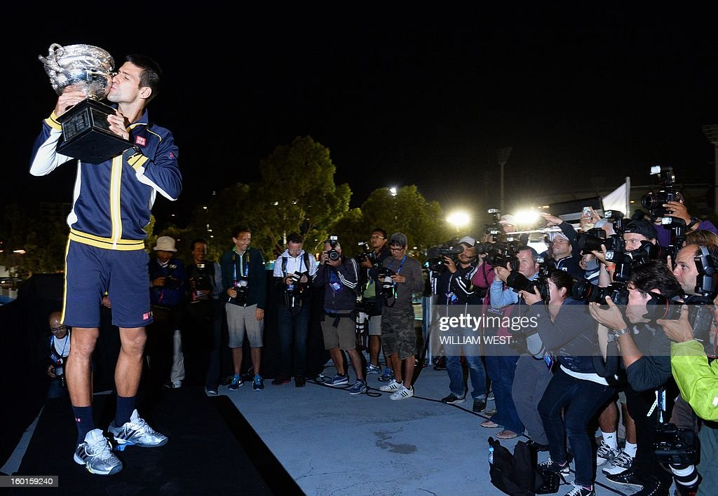 Serbia's Novak Djokovic for photographers during a presentation ceremony after his victory against Britain's Andy Murray in the men's singles final on day 14 of the Australian Open tennis tournament in Melbourne early on January 28, 2013. AFP PHOTO / WILLIAM WEST IMAGE STRICTLY RESTRICTED TO EDITORIAL USE - STRICTLY NO COMMERCIAL USE