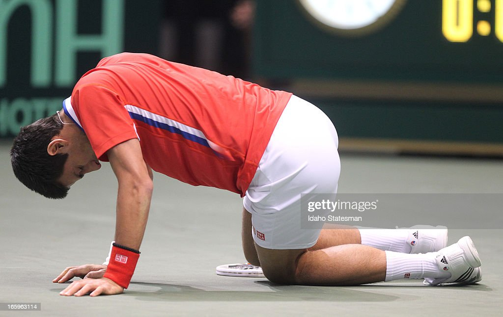 Serbia's Novak Djokovic hits the floor after injuring his right leg in a singles match against the United States' Sam Querrey during the Davis Cup quarterfinals in Boise, Idaho, Sunday, April 7, 2013.