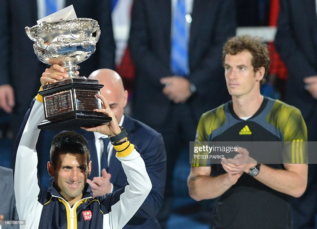 Serbia's Novak Djokovic hold up the trophy after his victory over Britain's Andy Murray (R) during the men's singles final on day 14 of the Australian Open tennis tournament in Melbourne on January 27, 2013. AFP PHOTO / PETER PARKS IMAGE STRICTLY RESTRICTED TO EDITORIAL USE - STRICTLY NO COMMERCIAL USE