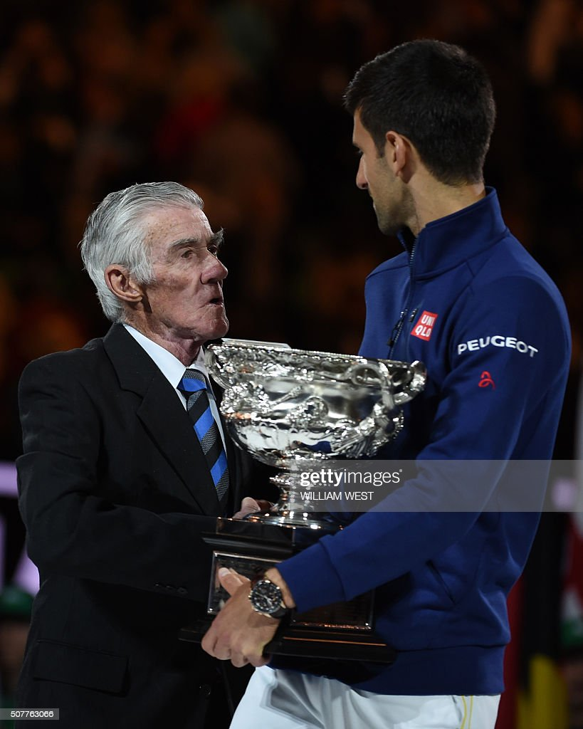Serbia s Novak Djokovic R holds The Norman Brookes Trophy as he
