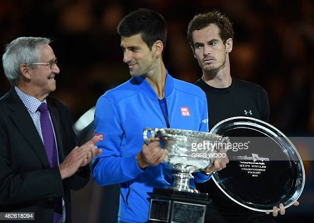 Serbia's Novak Djokovic holds The Norman Brookes Trophy towards former champion Roy Emerson after victory in men's singles final match against...