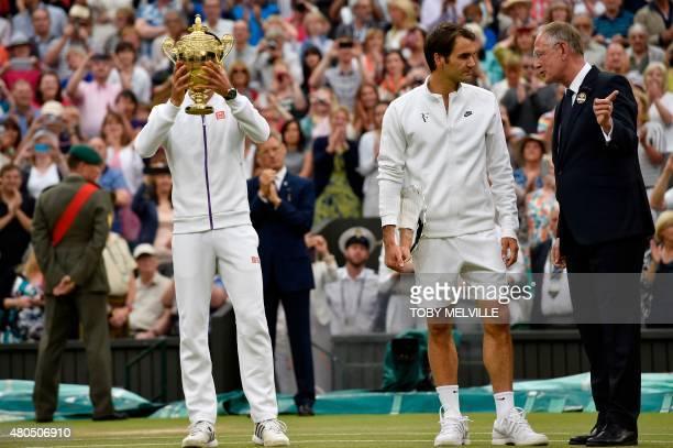 Serbia's Novak Djokovic holds the winner's trophy as he stands alongside Switzerland's Roger Federer after winning the men's singles final match...