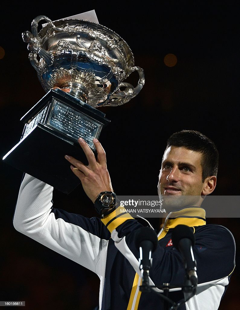 Serbia's Novak Djokovic holds up the winners trophy after his victory over Britain's Andy Murray during the men's singles final on day 14 of the Australian Open tennis tournament in Melbourne on January 27, 2013.