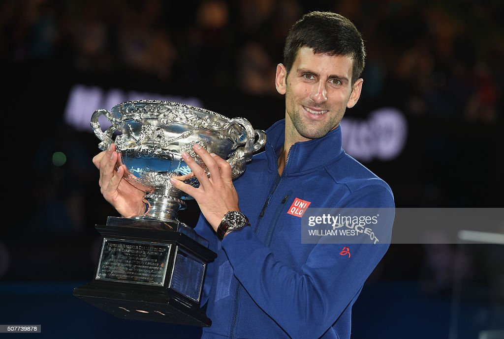 TOPSHOT - Serbia's Novak Djokovic poses with The Norman Brookes Trophy after victory in his men's singles final match against Britain's Andy Murray on day fourteen of the 2016 Australian Open tennis tournament in Melbourne on January 31, 2016.