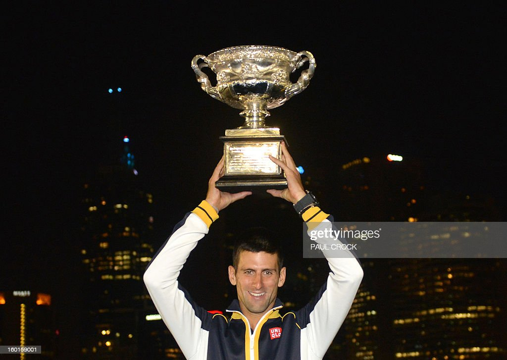 Serbia's Novak Djokovic poses with the trophy after victory in his men's singles final against Britain's Andy Murray on day fourteen of the Australian Open tennis tournament in Melbourne early January 28, 2013. AFP PHOTO/PAUL CROCK IMAGE STRICTLY RESTRICTED TO EDITORIAL USE - STRICTLY NO COMMERCIAL USE
