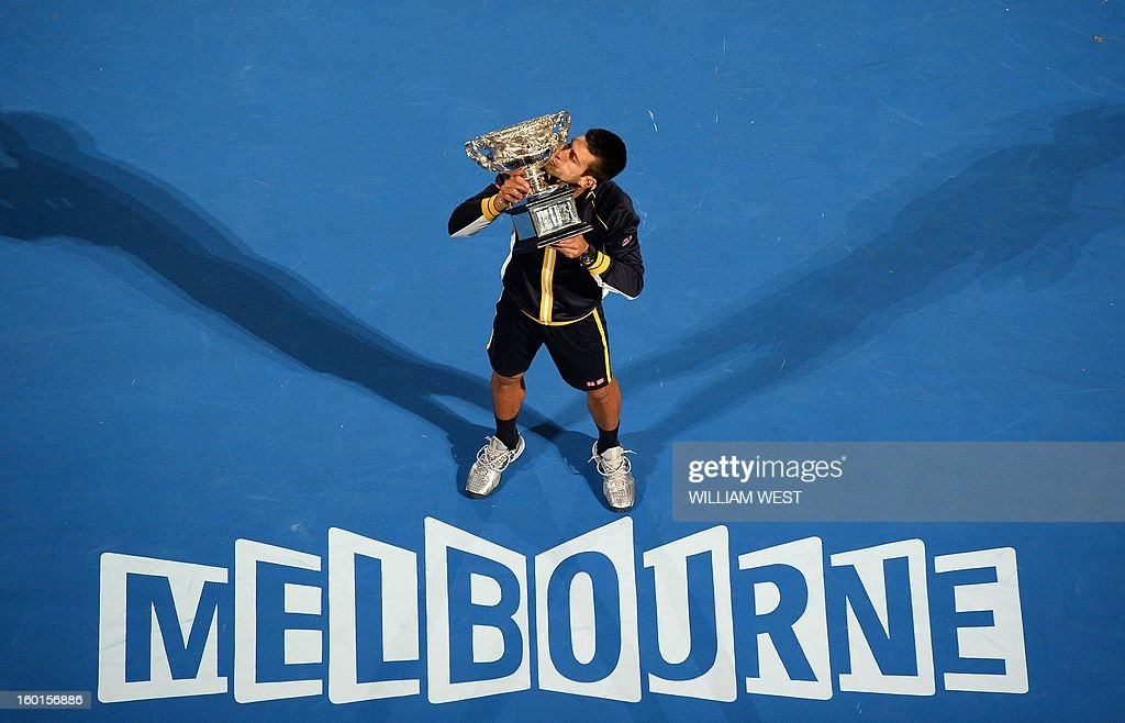 Serbia's Novak Djokovic poses with the winner's trophy after his victory over Britain's Andy Murray during the men's singles final on day 14 of the Australian Open tennis tournament in Melbourne on January 27, 2013.