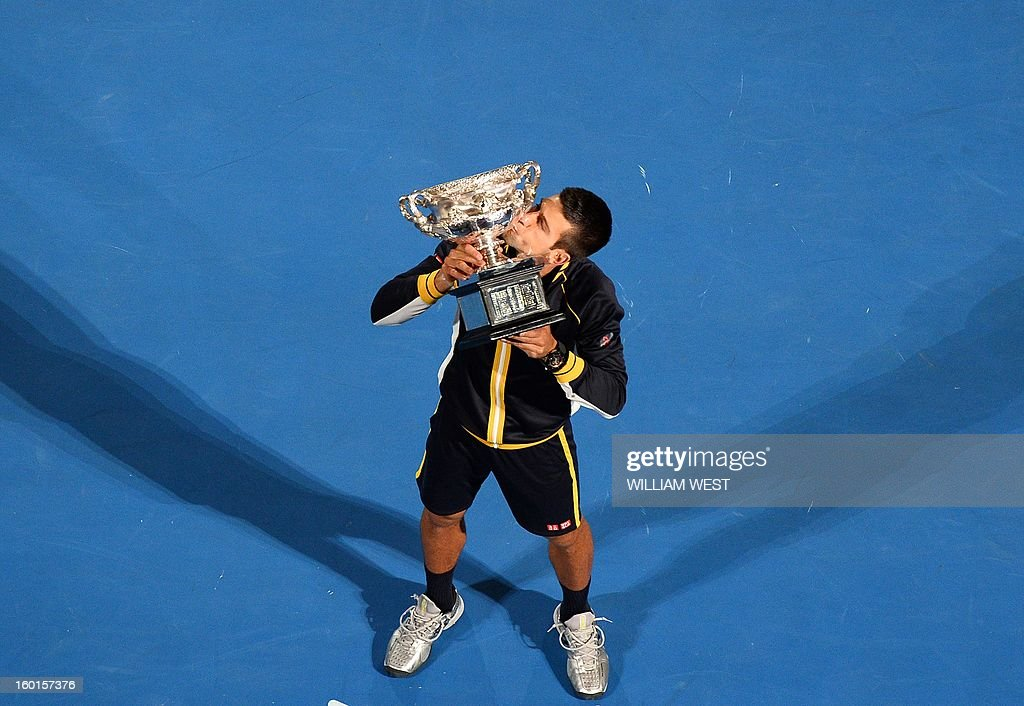 Serbia's Novak Djokovic poses with the winner's trophy after his victory over Britain's Andy Murray during the men's singles final on day 14 of the Australian Open tennis tournament in Melbourne on January 27, 2013. AFP PHOTO / WILLIAM WEST IMAGE STRICTLY RESTRICTED TO EDITORIAL USE - STRICTLY NO COMMERCIAL USE