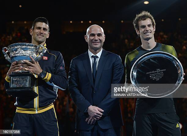 Serbia's Novak Djokovic poses with the winner's trophy alongside Andre Agassi after his victory over Britain's Andy Murray during the men's singles...