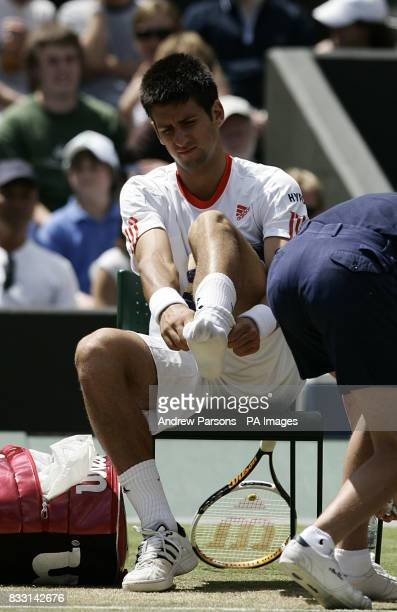 Serbia's Novak Djokovic puts on another sock after receiving treatment on his foot during his semifinal match against Spain's Rafael Nadal during The...