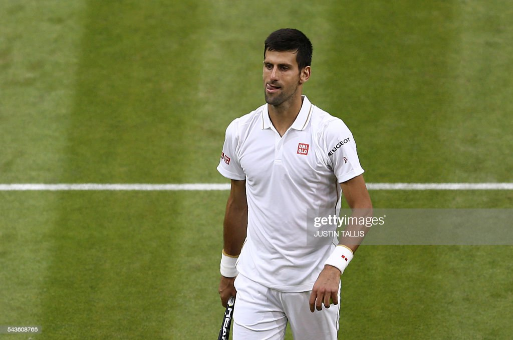 Serbia's Novak Djokovic reacts during his men's singles second round match against France's Adrian Mannarino on the third day of the 2016 Wimbledon Championships at The All England Lawn Tennis Club in Wimbledon, southwest London, on June 29, 2016. / AFP / JUSTIN