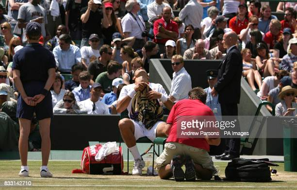 Serbia's Novak Djokovic receives treatment on his foot during his semifinal match against Spain's Rafael Nadal during The All England Lawn Tennis...