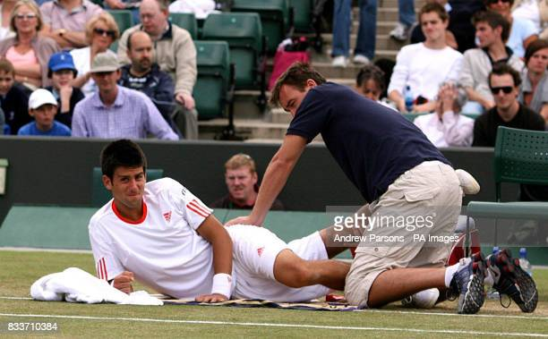 Serbia's Novak Djokovic recieves treatment during his match against Cyprus' Marcos Baghdatis during The All England Lawn Tennis Championship at...