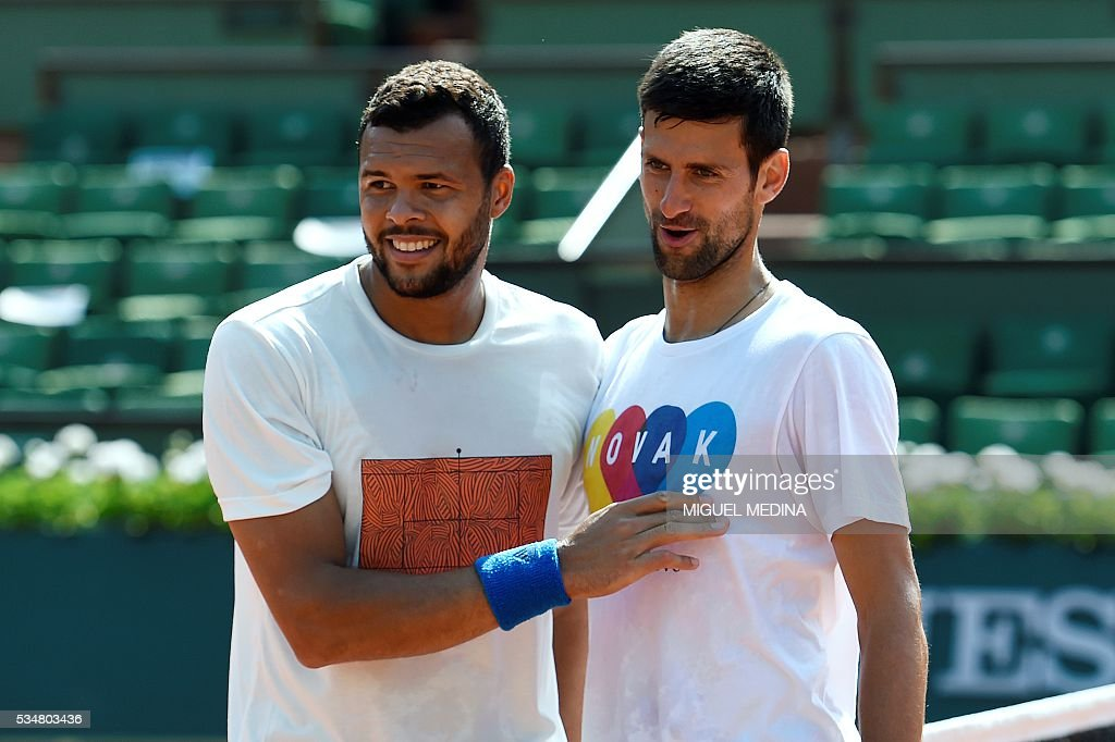 Serbia's Novak Djokovic (R) shakes hands with France's Jo-Wilfried Tsonga after their training session at the Roland Garros 2016 French Tennis Open in Paris on May 28, 2016. / AFP / MIGUEL