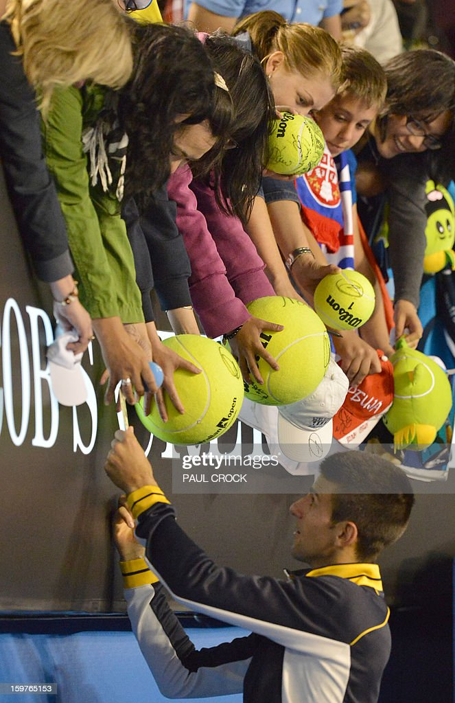 Serbia's Novak Djokovic signs autographs as he celebrates after victory in his men's singles match against Switzerland's Stanislas Wawrinka on the seventh day of the Australian Open tennis tournament in Melbourne early January 21, 2013.