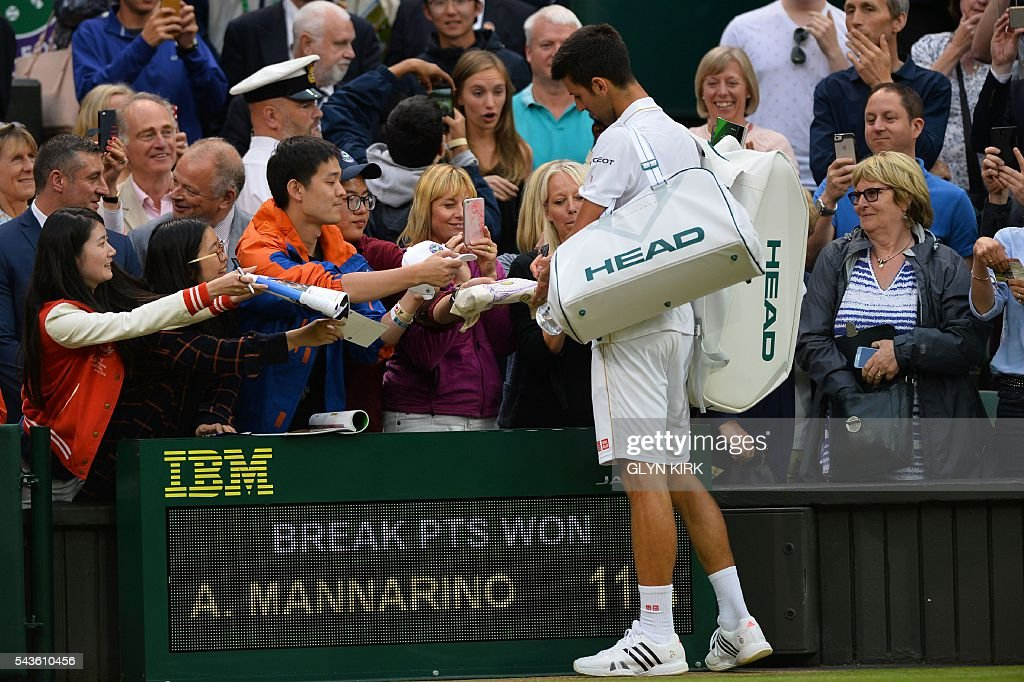 Serbia's Novak Djokovic signs autographs for fans after beating France's Adrian Mannarino in their men's singles second round match on the third day of the 2016 Wimbledon Championships at The All England Lawn Tennis Club in Wimbledon, southwest London, on June 29, 2016. / AFP / GLYN