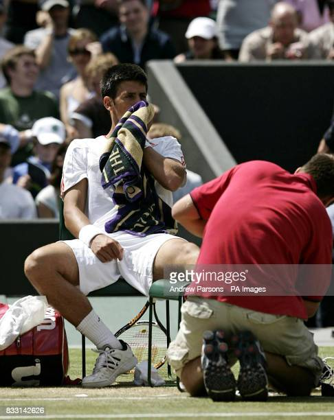 Serbia's Novak Djokovic sits dejected as he receives treatment during his semifinal match against Spain's Rafael Nadal during The All England Lawn...