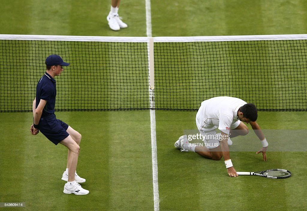 Serbia's Novak Djokovic slips while playing a shot against France's Adrian Mannarino during their men's singles second round match on the third day of the 2016 Wimbledon Championships at The All England Lawn Tennis Club in Wimbledon, southwest London, on June 29, 2016. / AFP / JUSTIN