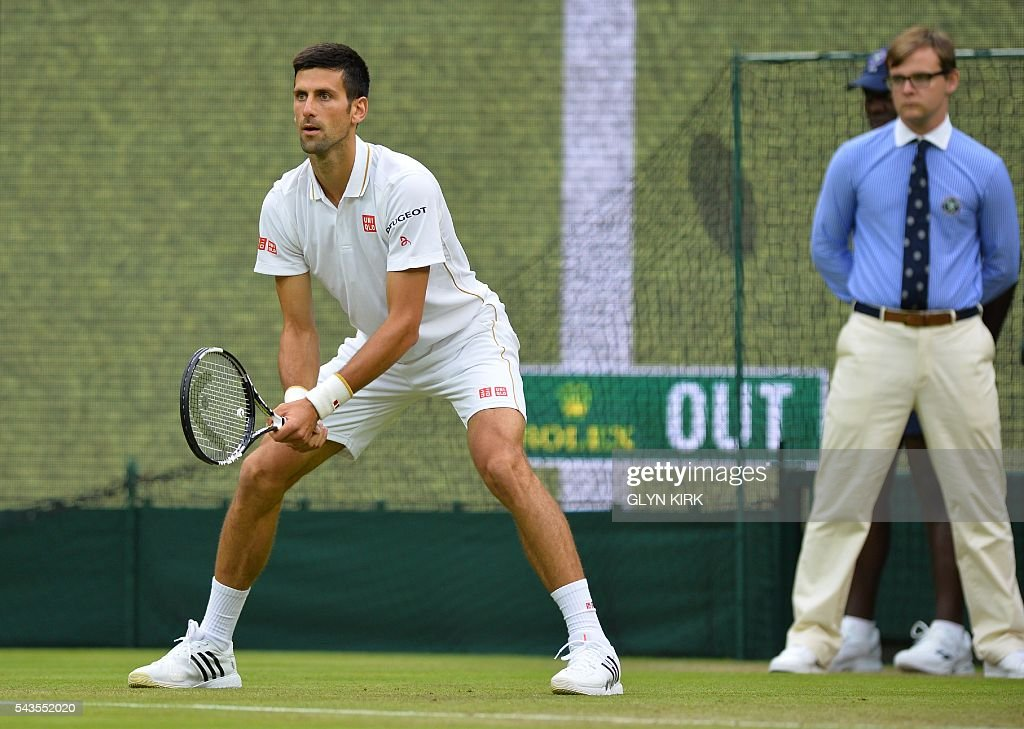 Serbia's Novak Djokovic stands on the baseline as the screen behind him shows the result of a challenge against France's Adrian Mannarino during their men's singles second round match on the third day of the 2016 Wimbledon Championships at The All England Lawn Tennis Club in Wimbledon, southwest London, on June 29, 2016. / AFP / GLYN