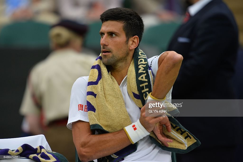 Serbia's Novak Djokovic stretches as he sits in the break between games against France's Adrian Mannarino during their men's singles second round match on the third day of the 2016 Wimbledon Championships at The All England Lawn Tennis Club in Wimbledon, southwest London, on June 29, 2016. / AFP / GLYN