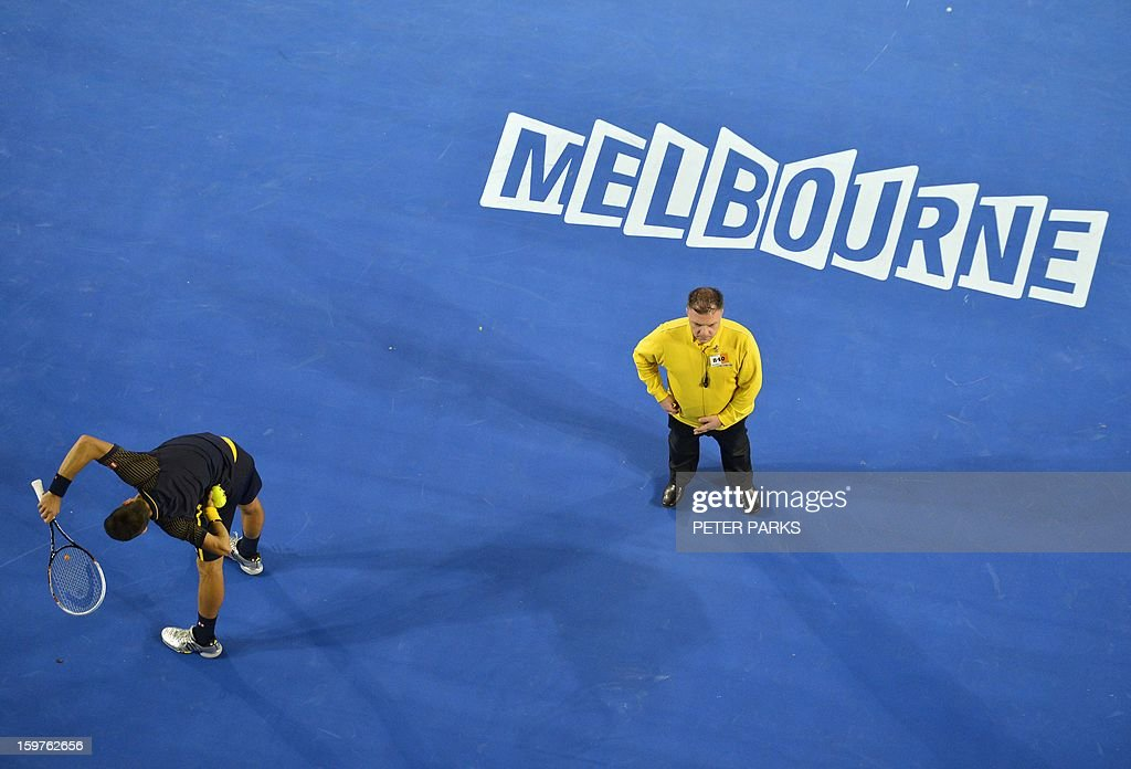 Serbia's Novak Djokovic (L) stretches during his men's singles against Switzerland's Stanislas Wawrinka match on day seven of the Australian Open tennis tournament in Melbourne on January 20, 2013.