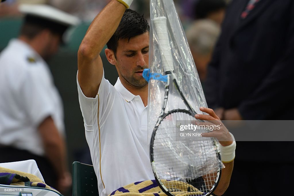 Serbia's Novak Djokovic takes a fresh racquet from its wrapper in the break between games against France's Adrian Mannarino during their men's singles second round match on the third day of the 2016 Wimbledon Championships at The All England Lawn Tennis Club in Wimbledon, southwest London, on June 29, 2016. / AFP / GLYN
