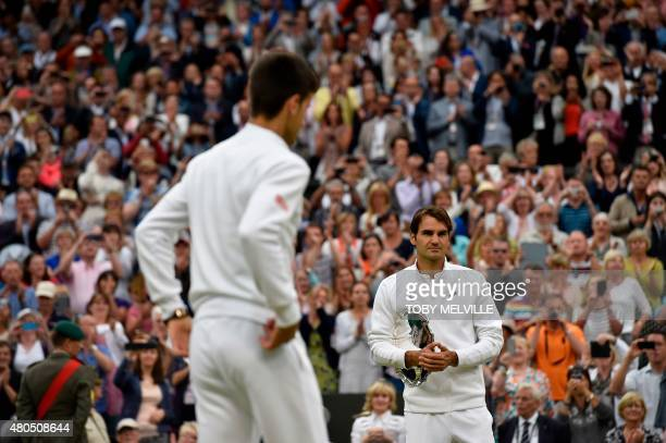 Serbia's Novak Djokovic waits to receive the winners trophy after beating Switzerland's Roger Federer during their men's singles final match on...