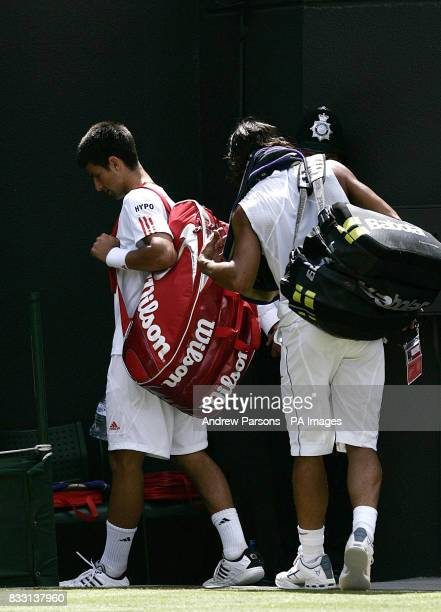 Serbia's Novak Djokovic walks from the Court followed by Spain's Rafael Nadal after conceding the match during The All England Lawn Tennis...
