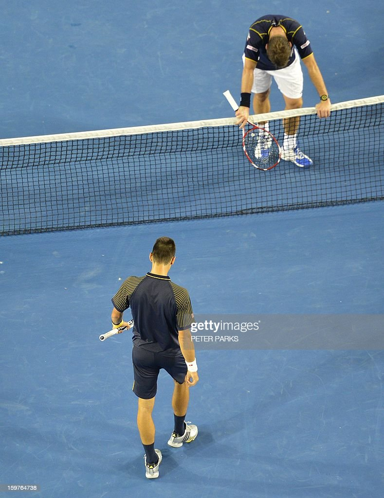 Serbia's Novak Djokovic (LOWER) walks towards Switzerland's Stanislas Wawrinka after his victory during their men's singles match on day seven of the Australian Open tennis tournament in Melbourne early on January 21, 2013.