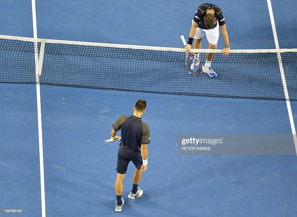 Serbia's Novak Djokovic (LOWER) walks towards Switzerland's Stanislas Wawrinka following his victory during their men's singles match on day seven of the Australian Open tennis tournament in Melbourne early on January 21, 2013.
