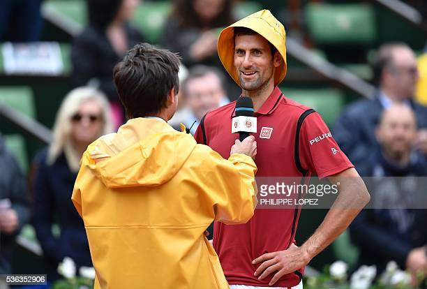 TOPSHOT Serbia's Novak Djokovic wears a yellow rain hat as he is interviewed by former French tennis player Fabrice Santoro after winning his men's...