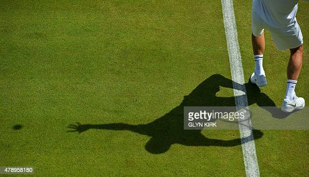 Serbia's Novak Djokovic's training parter serves to him during a practice session on day one of the 2015 Wimbledon Championships at The All England...