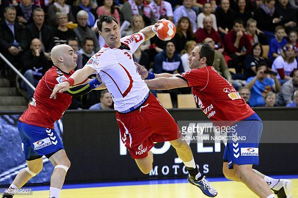 Serbia's pivot Alem Toskic and his teammate left back Momir Ilic try to stop Poland's right back Krzysztof as he jumps to score during the men's EHF...