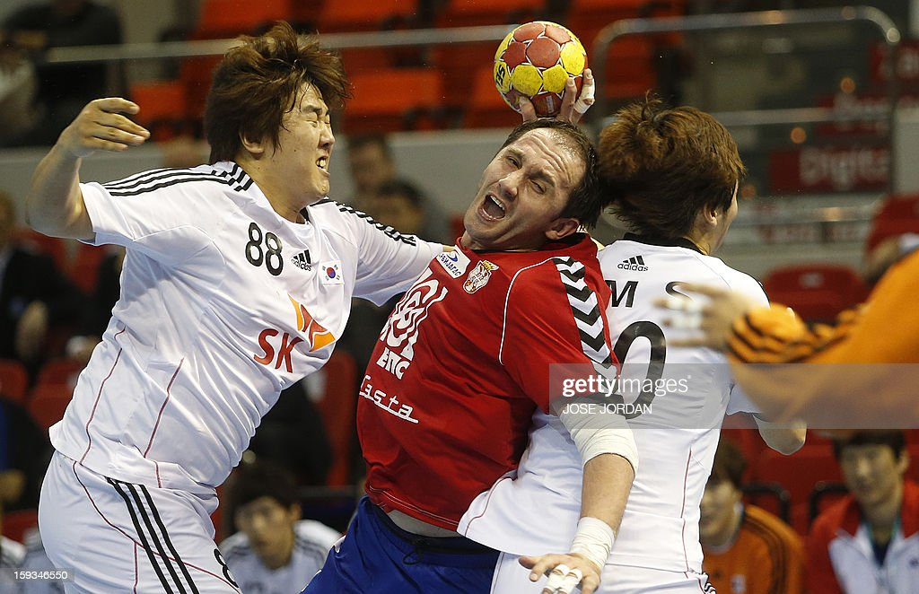 Serbia's pivot Alem Toskic (C) vies with Korea's back Yun-Suk Oh during the 23rd Men's Handball World Championships preliminary round Group C match Serbia vs Korea at the Pabellon Principe Felipe in Zaragoza on January 12, 2013. AFP PHOTO/ JOSE JORDAN