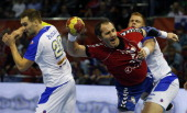 Serbia's pivot Alem Toskic vies with Slovenia's left wing Luka Zvizej and Slovenia's pivot Matej Gaber during the 23rd Men's Handball World...