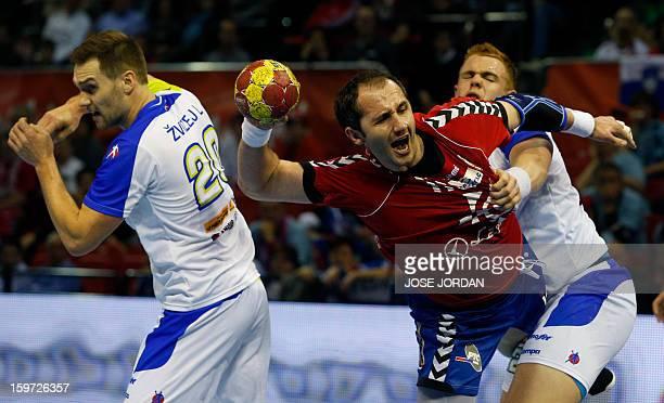Serbia's pivot Alem Toskic vies with Slovenia's left wing Luka Zvizej and Slovenia's pivot Matej Gaber during the 23rd Men's Handball World...