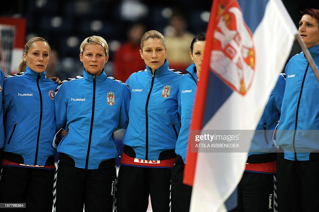 Serbia's players sing their national anthem prior to the 2012 EHF European Women's Handball Championship match against Ukraine on December 6, 2012, at the Kombank Arena of Belgrade. The Serbian capital Belgrade hosts the preliminary round Group A matches including Czech Republic, Norway, Serbia and Ukraine. AFP PHOTO / ATTILA KISBENEDEK
