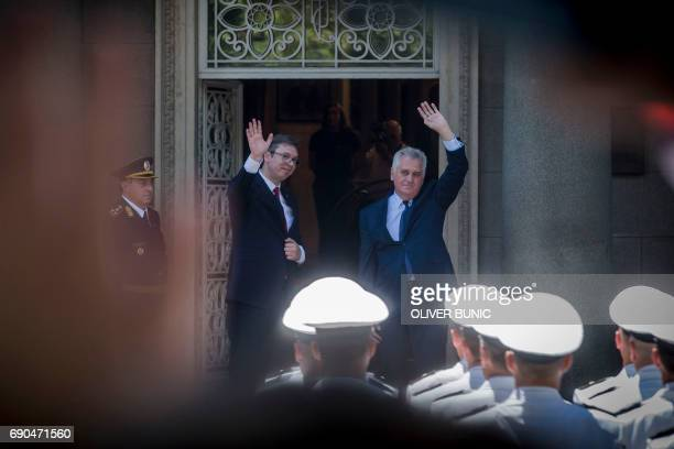 Serbia's Presidentelect Aleksandar Vucic waves with former President Tomislav Nikolic prior to take oath at the national assembly in Belgrade on May...