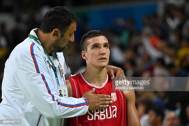 Serbia's shooting guard Bogdan Bogdanovic reacts next to former basketball player Vlade Divac after losing to USA during a Men's round Group A...