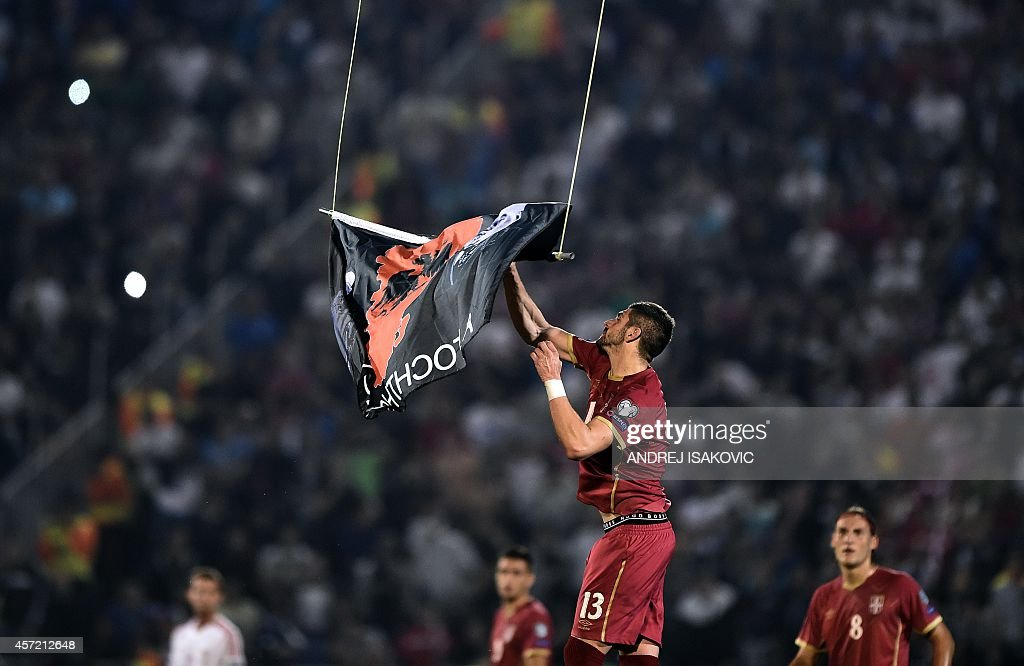 Serbia's Stefan Mitrovic grabs a flag with Albanian national symbols flown by a remotely operated drone during the Euro 2016 group I football match...
