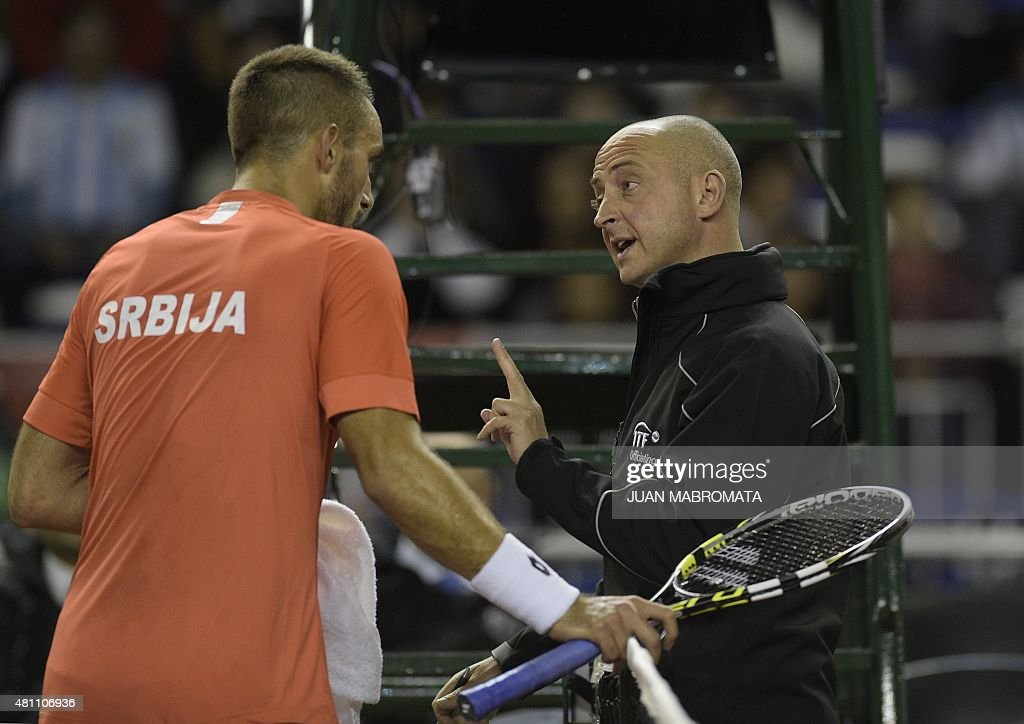 Serbia's tennis player Viktor Troicki and chair umpire Pascal Maria speak during the Davis Cup World Group quarterfinal single tennis match against...
