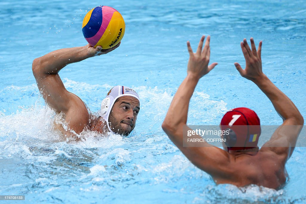 Serbia's Vanja Udovicic scores against Romania's goalkeeper Dragos Stoenescu during their men's water polo quarterfinals qualification match at the...