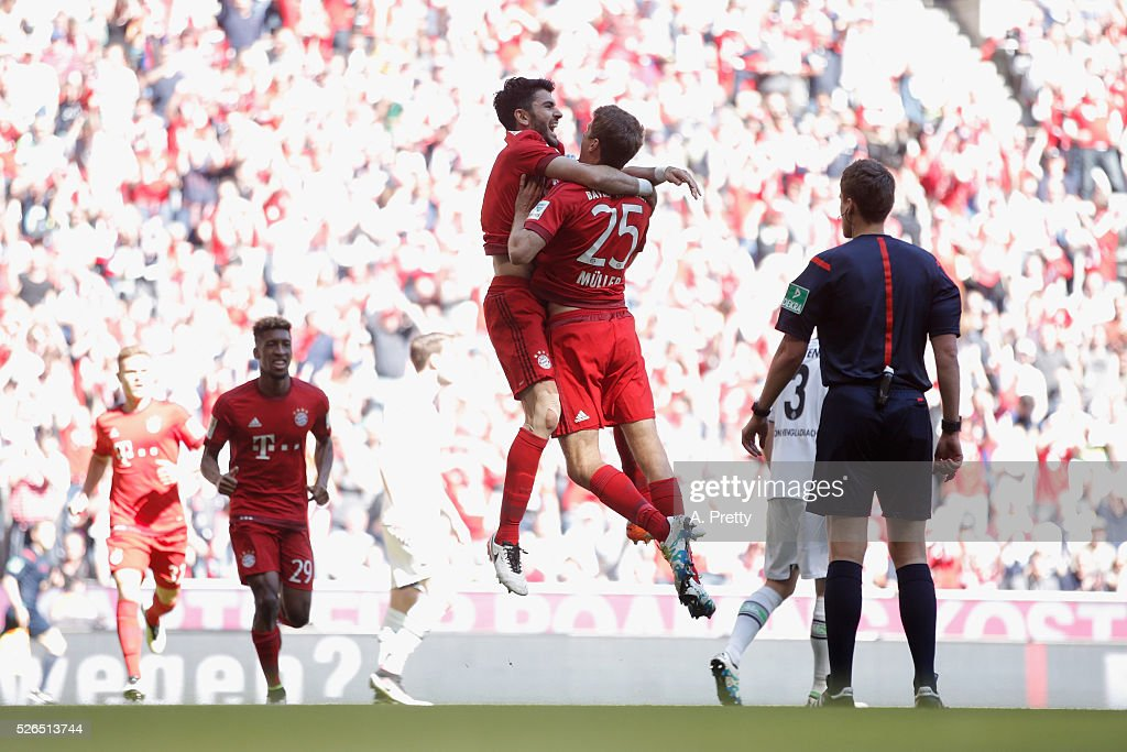 Serdar Tasci (C) of Bayern Muenchen celebrates scoring his team's first goal with his team mate Thomas Mueller (C-R) during the Bundesliga match between Bayern Muenchen and Borussia Moenchengladbach at Allianz Arena on April 30, 2016 in Munich, Germany.
