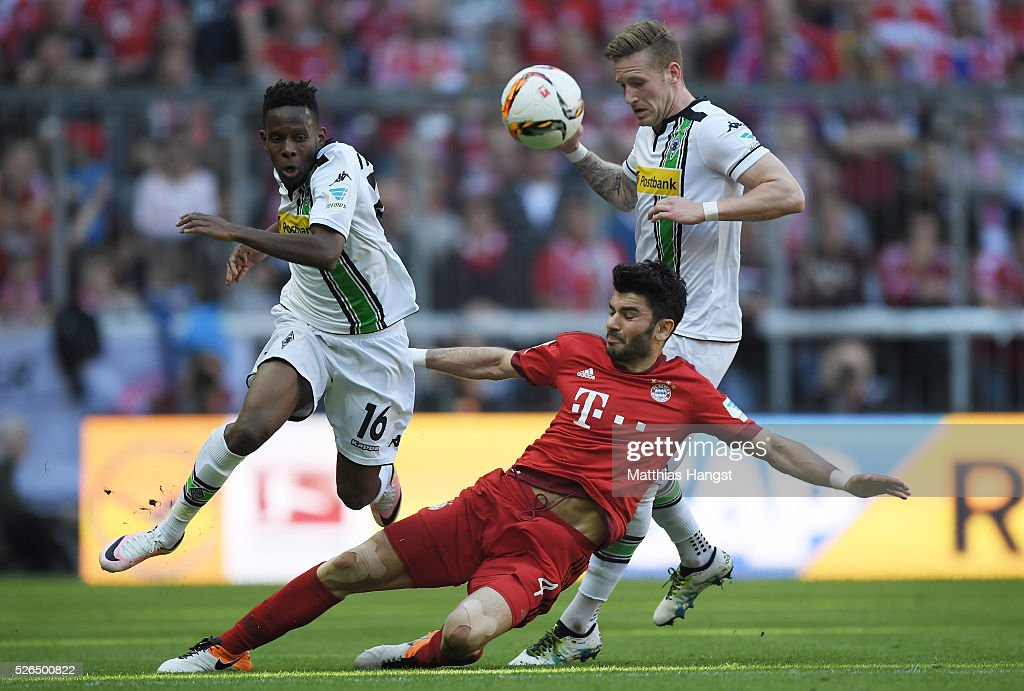 Serdar Tasci (C) of Bayern Muenchen competes for the ball against Ibrahima Traore (L) and Andre Hahn (R) of Borussia Moenchengladbach during the Bundesliga match between Bayern Muenchen and Borussia Moenchengladbach at Allianz Arena on April 30, 2016 in Munich, Germany.